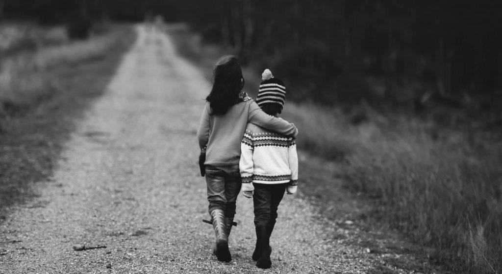grayscale children walking down track