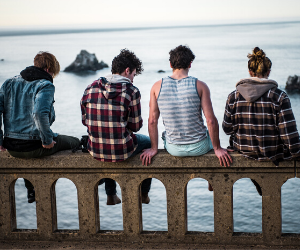 four boys sitting in front of sea